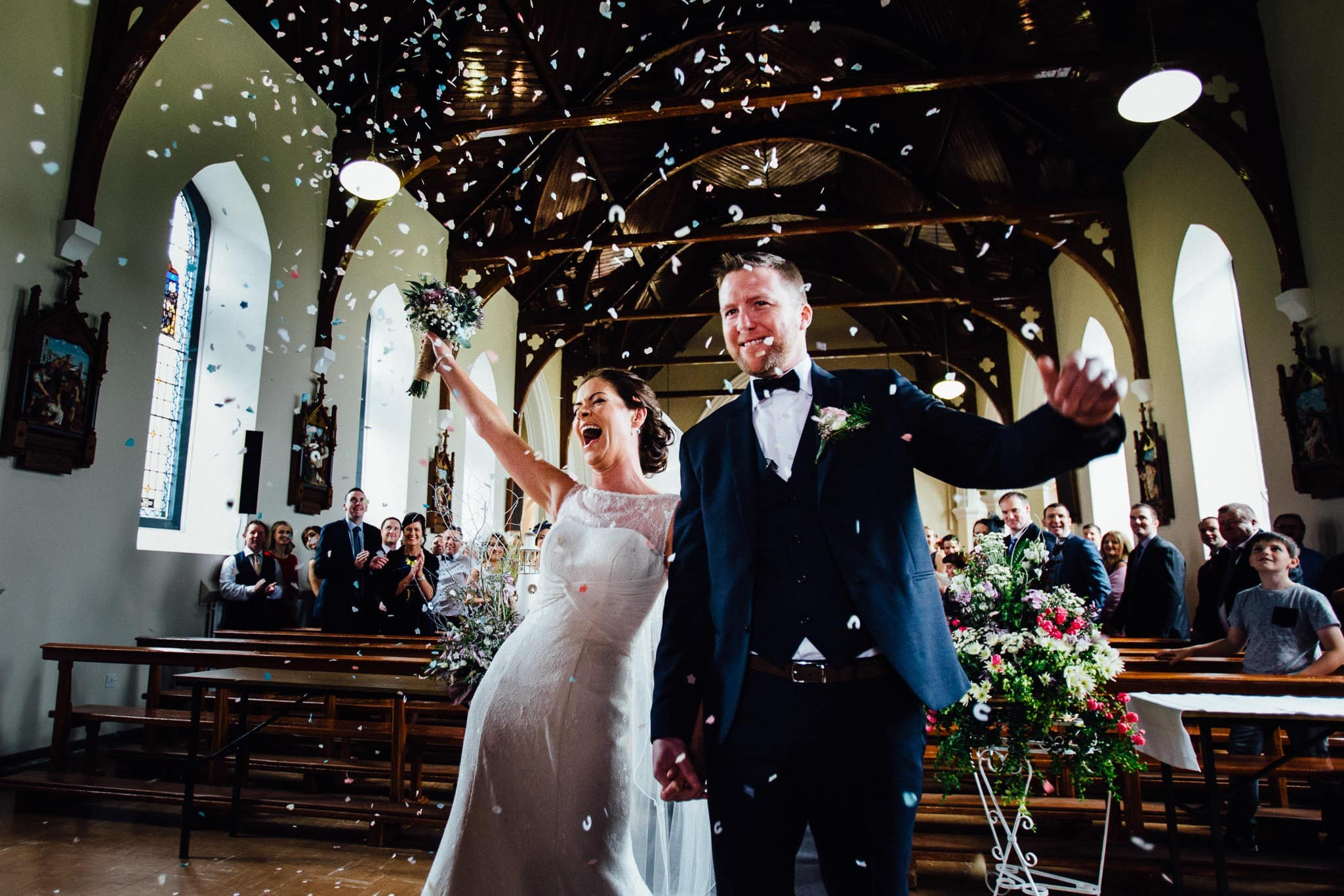 Bride and groom get confetti thrown at them on the way out of the church