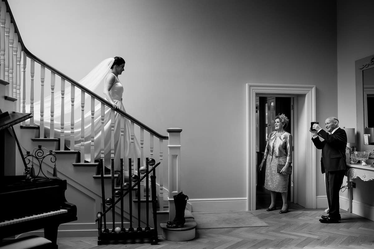 Bride walks down the stairs on the morning of her wedding to her parents as her dad takes a photo of her on his phone