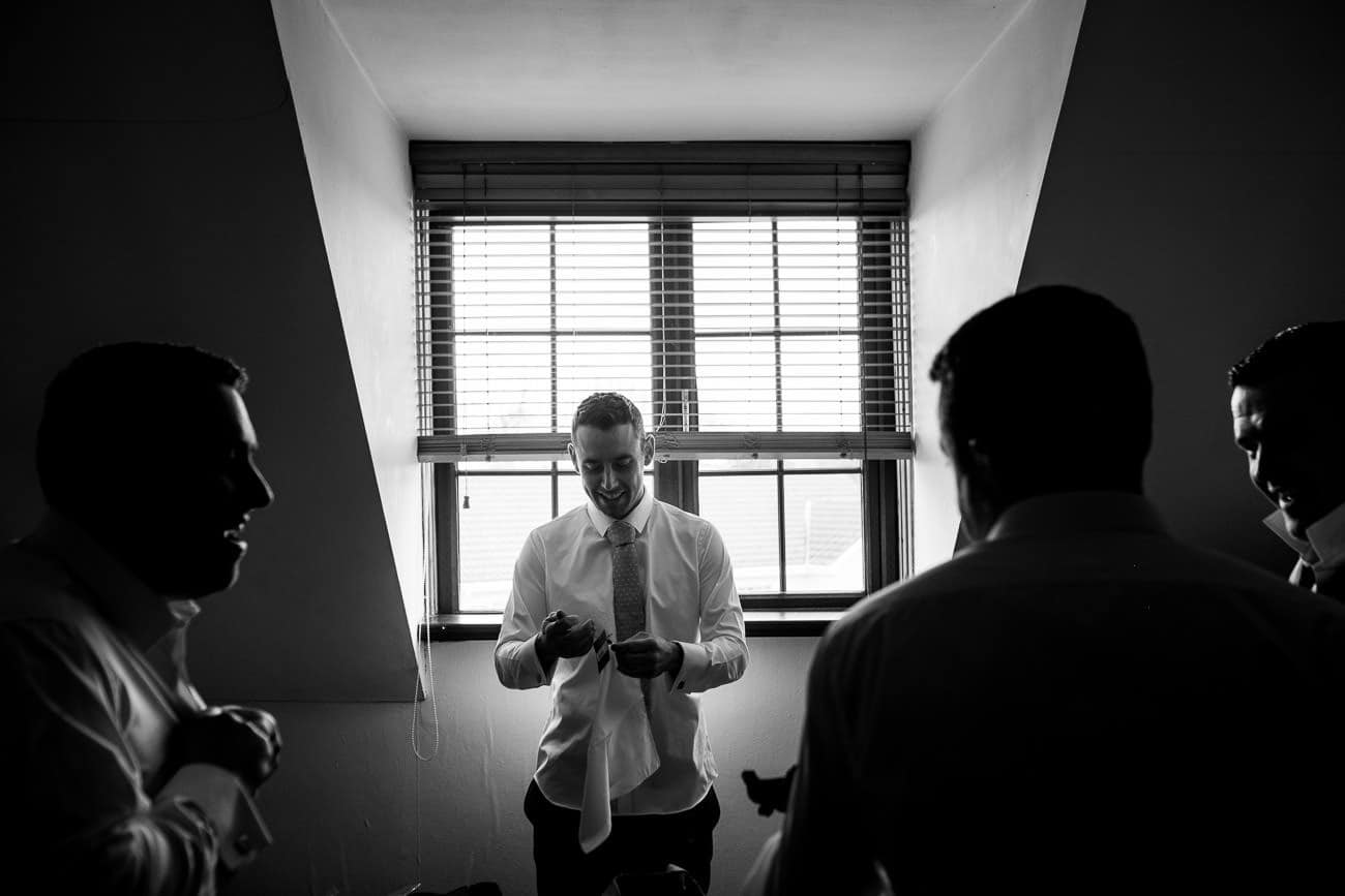 A groom gets dressed with his groomsmen