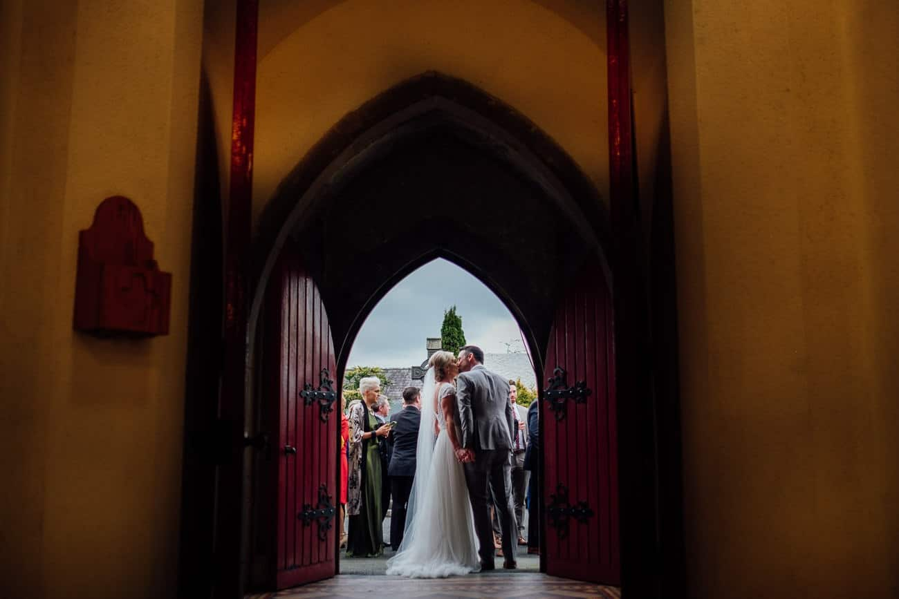 the bride and groom kiss at outside the church