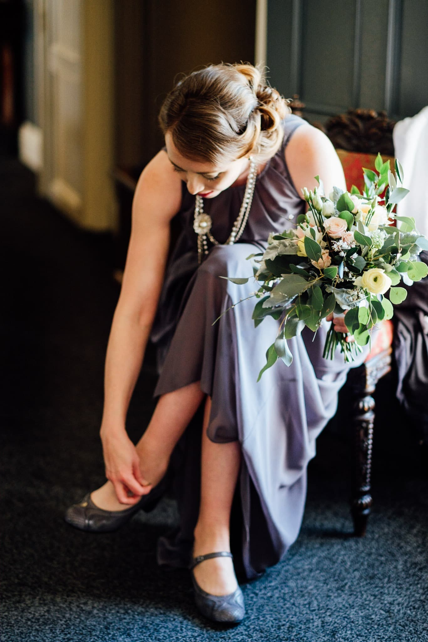 bridesmaid puts her shoes on