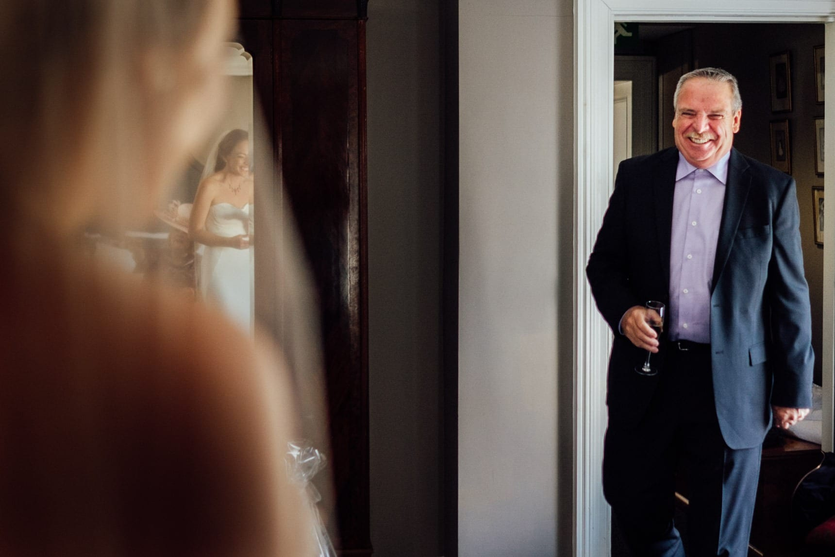Father of the bride sees her daughter for the first time in her wedding dress