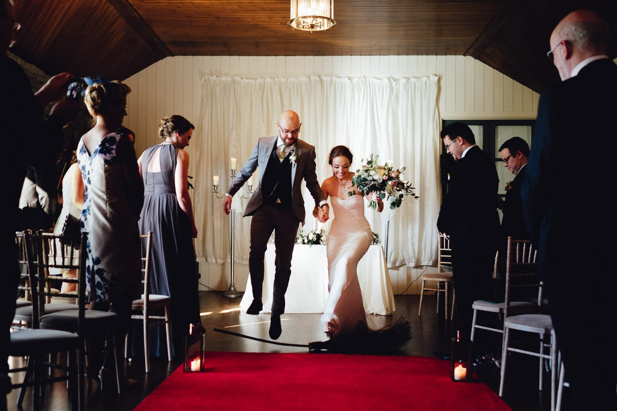 bride and groom jump over a broom and the end of their wedding ceremony