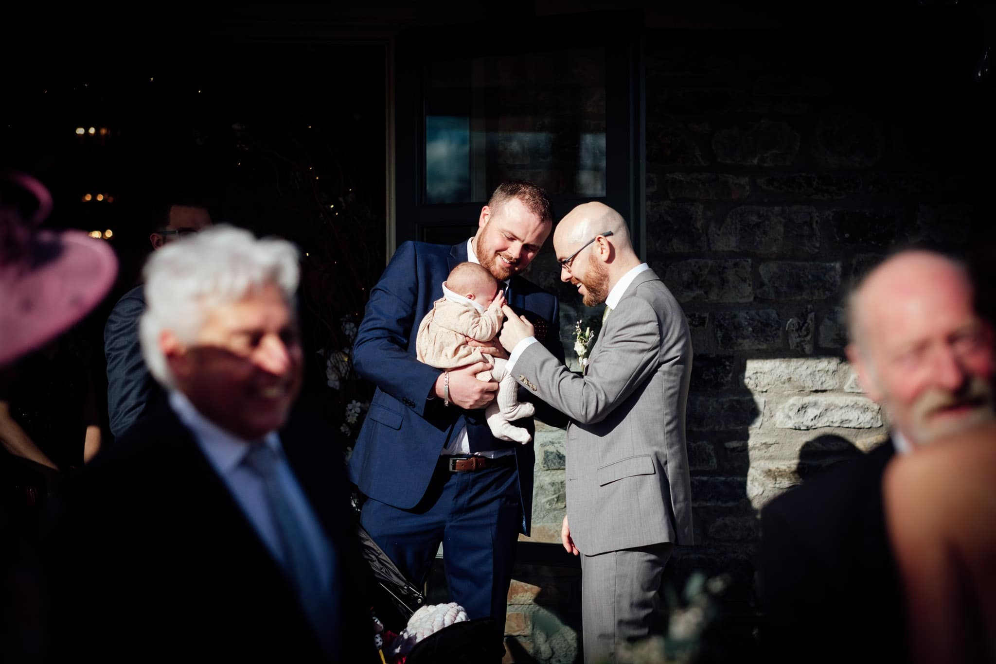 groom smiling at a baby outside the ceremony room