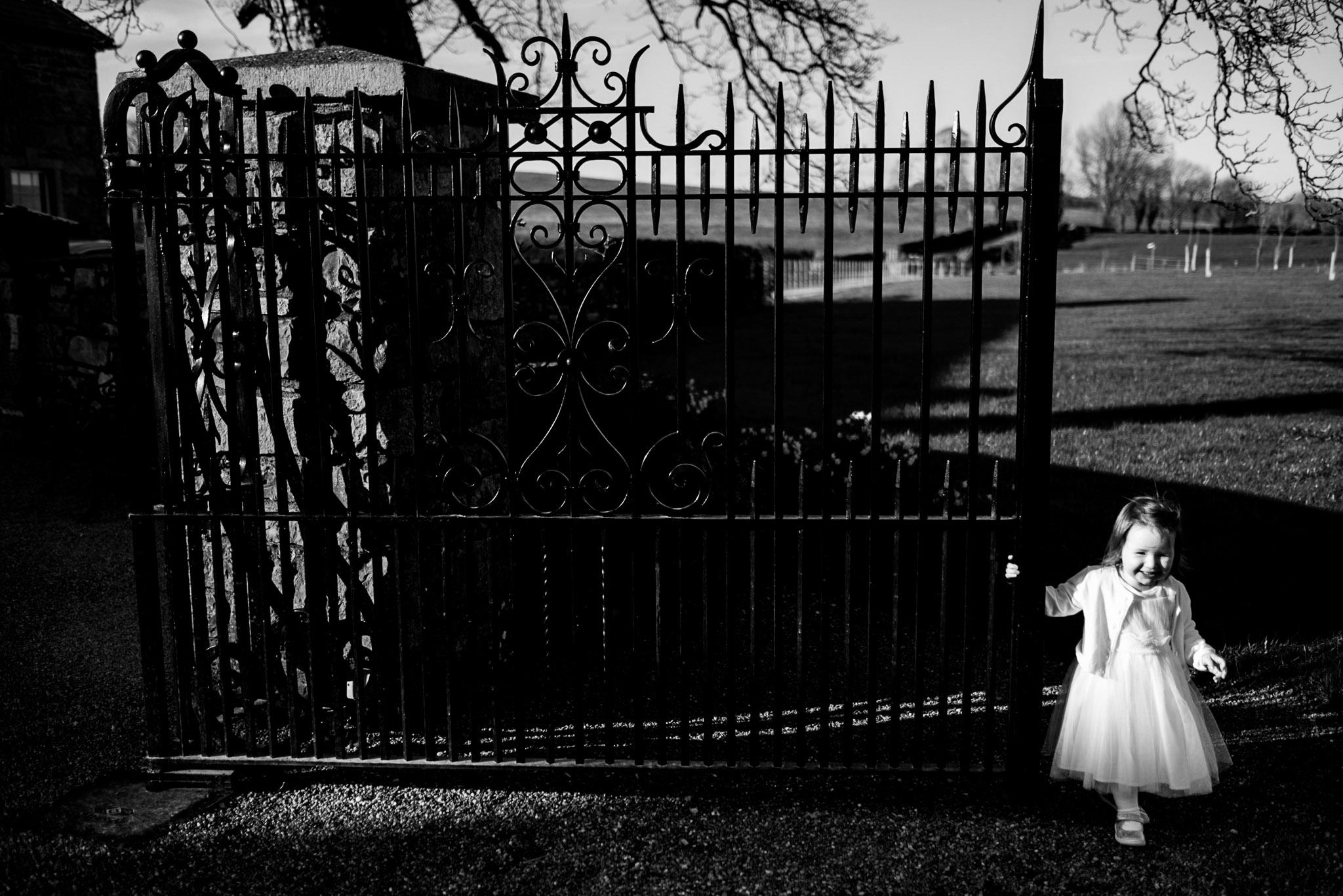 flower girl stands beside a gate