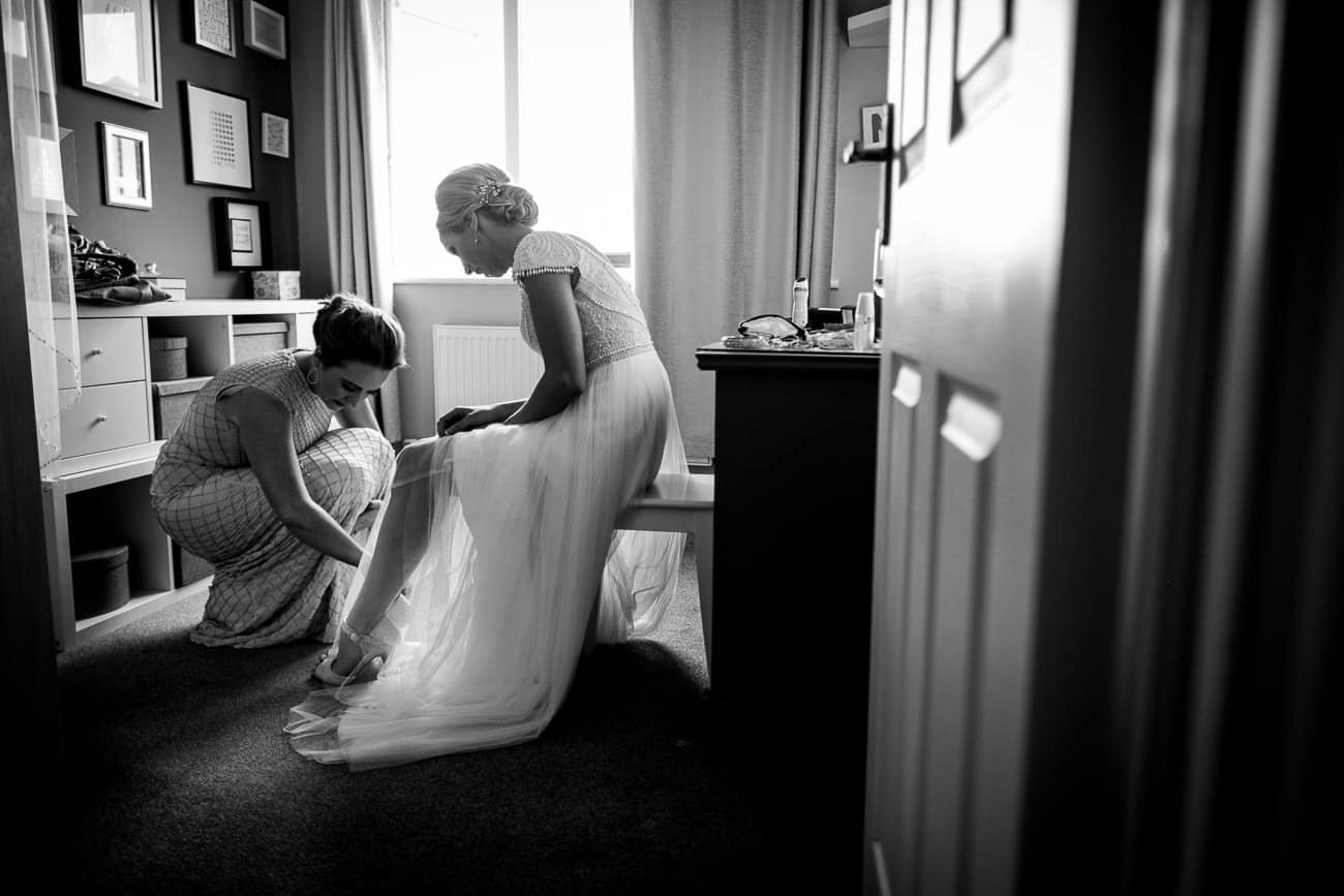 A bridesmaid puts on the brides shoes