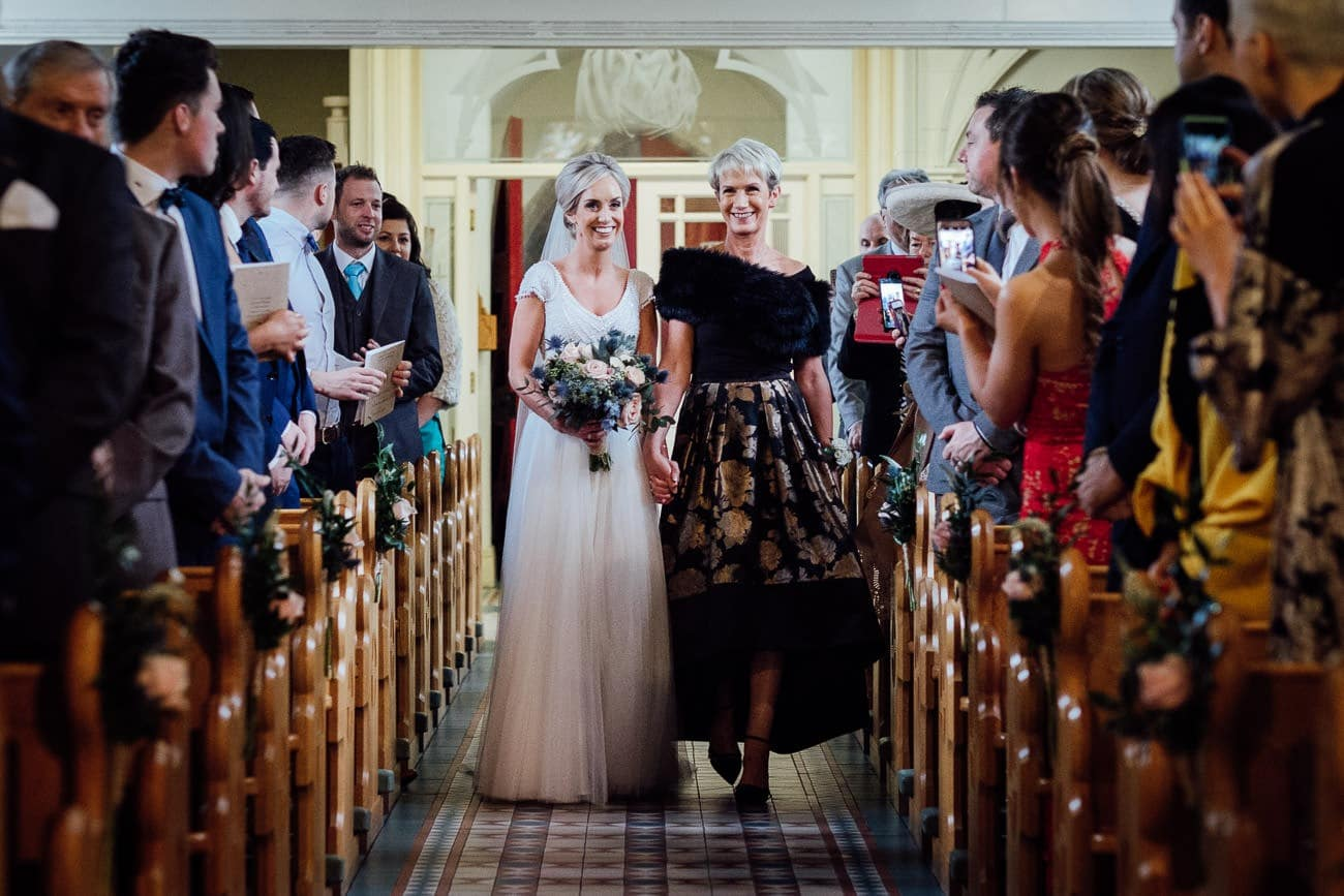 The bride walks down the church aisle with her Mother