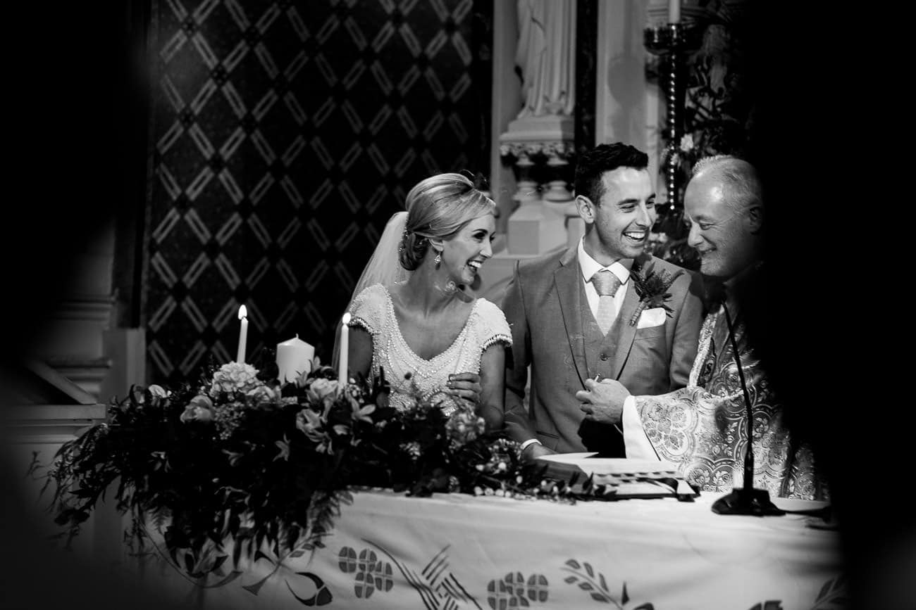 the bride and groom joke with the priest
