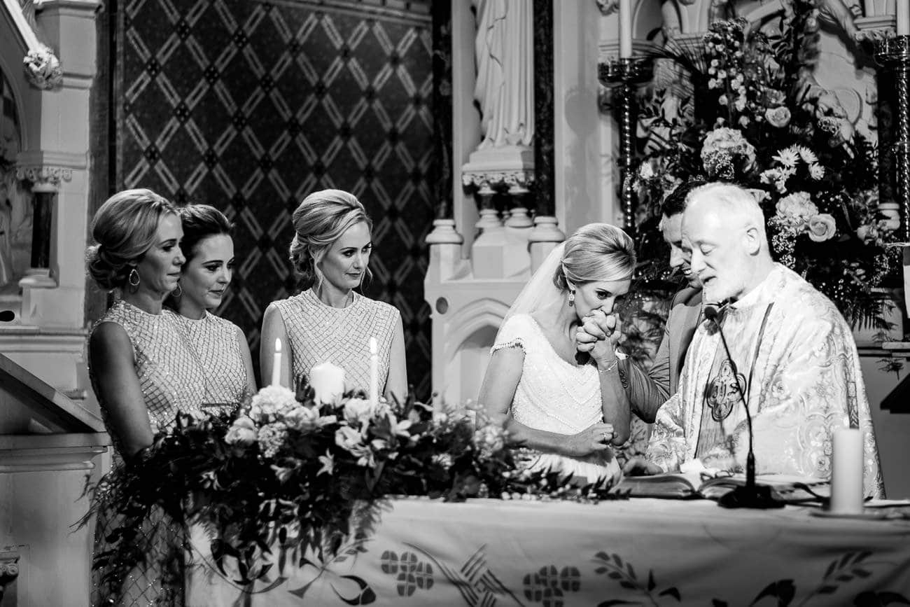 The bride and groom exchange vows on the altar with the bridal party