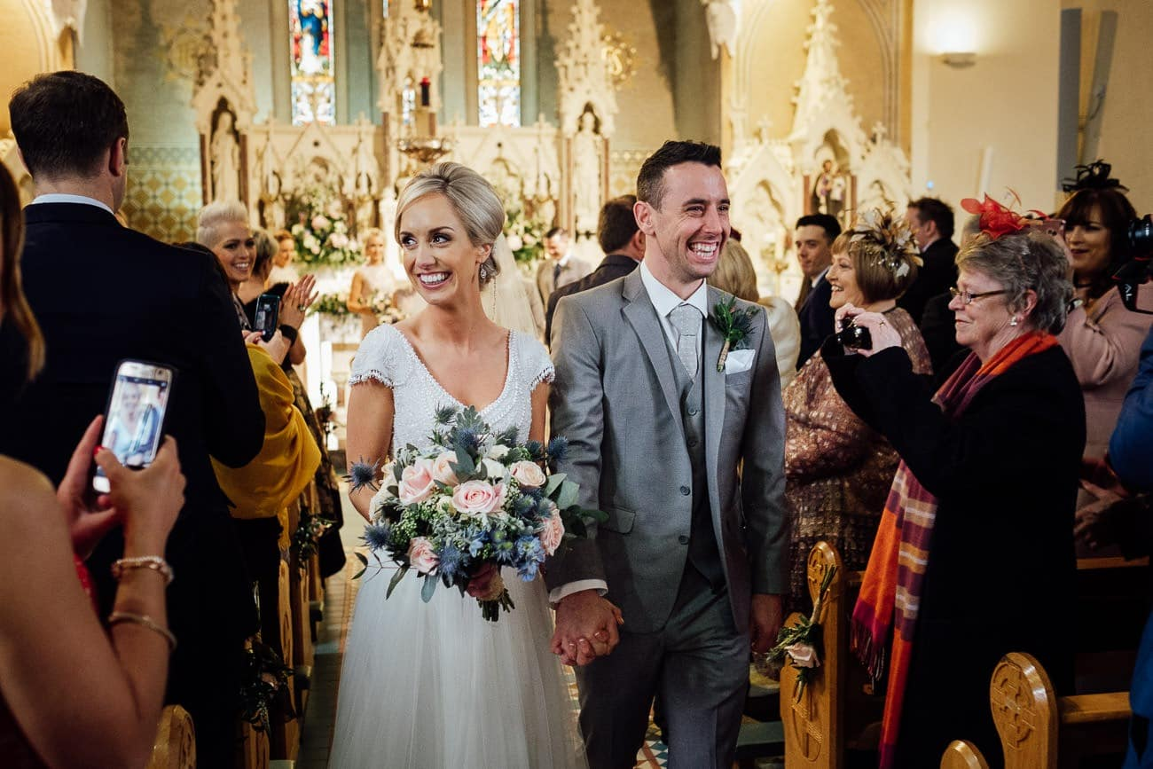 the bride and groom walk down the aisle