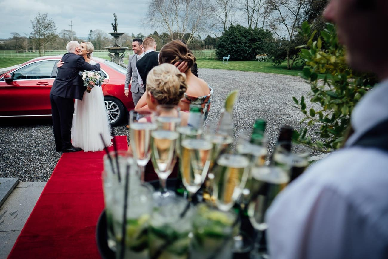 the bride steps out of the car at a ballymagarvey village wedding