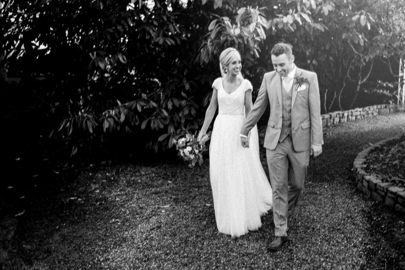 The bride and groom walk through the grounds of Ballymagarvey