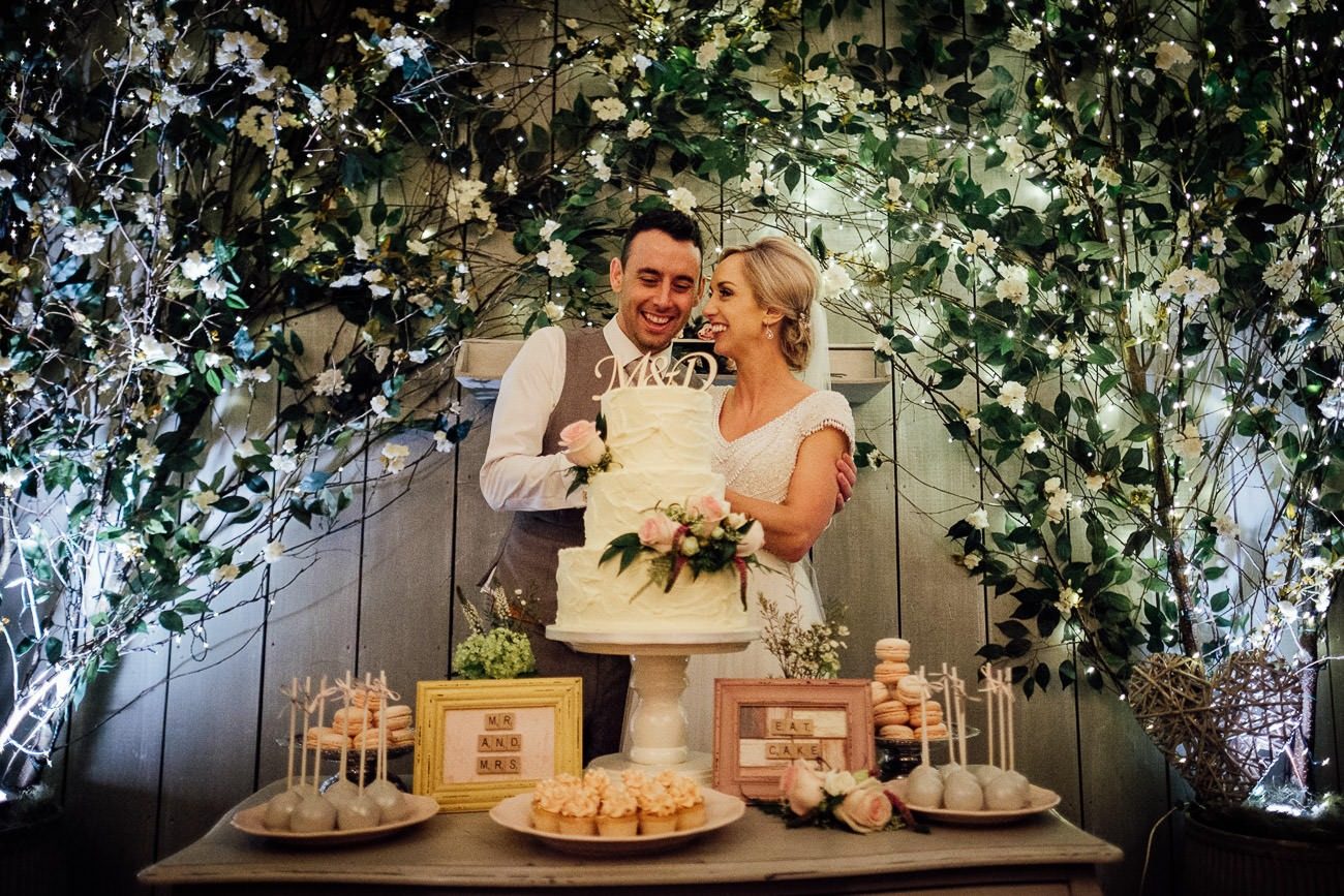 the bride and groom cut the cake at Ballymagarvey Village