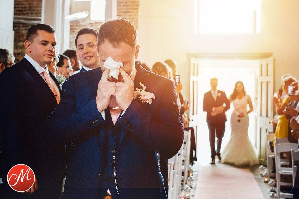 A teary eyed groom awaits his bride at The Millhouse